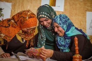 Female refugees looking at embroidery