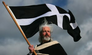 An actor dressed as St Piran, considered to be Cornwall's patron saint, waves the St Piran flag.