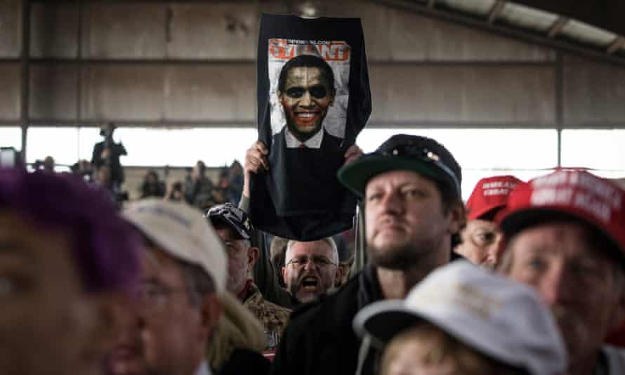 A man holds up an image of Barack Obama with the word 'tyrant' above itduring a Trump rally in Colorado Springs.