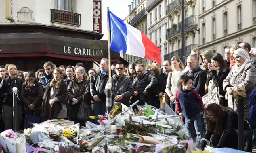 People observe a minute's silence at the Le Carillon cafe, where 15 people were killed.