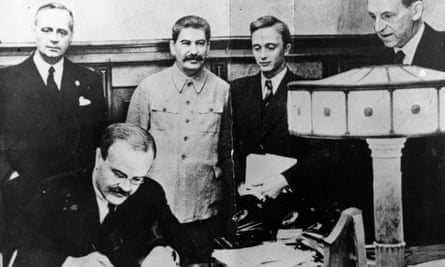 Vyacheslav Molotov, Russian foreign minister, signs the non-aggression pact negotiated between Soviet Russia and Germany, at the Kremlin, Moscow. Standing behind him is his German counterpart Joachim von Ribbentrop (left), and Joseph Stalin (centre), 23 August 1939.