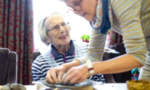 A care home resident is guided with her clay modelling.