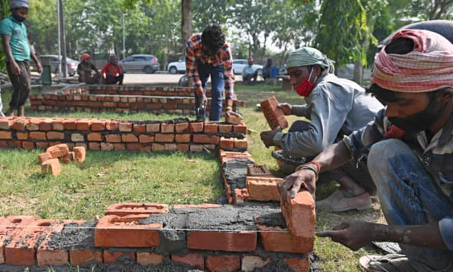 Workers are seen constructing makeshift platforms for funeral pyres in a park inside the premises of a crematorium in Delhi