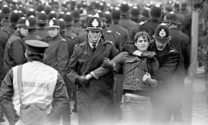 A picket is led away during the Orgreave clash in 1984.