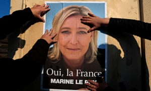 Supporters paste a poster of Marine Le Pen, France's National Front leader, on a wall