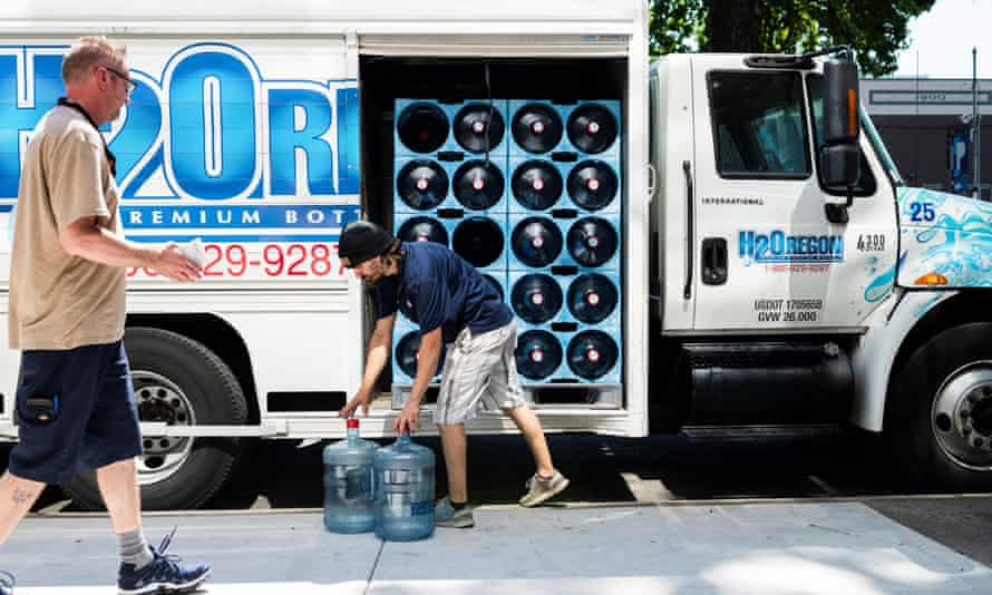 Crosby Lundbom and Destin Hornych make a water delivery during the heatwave in Portland, Oregon