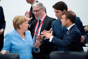 The French president, Emmanuel Macron (right), speaks with Germany's chancellor, Angela Merkel, and the Canadian prime minister, Justin Trudeau (second right)