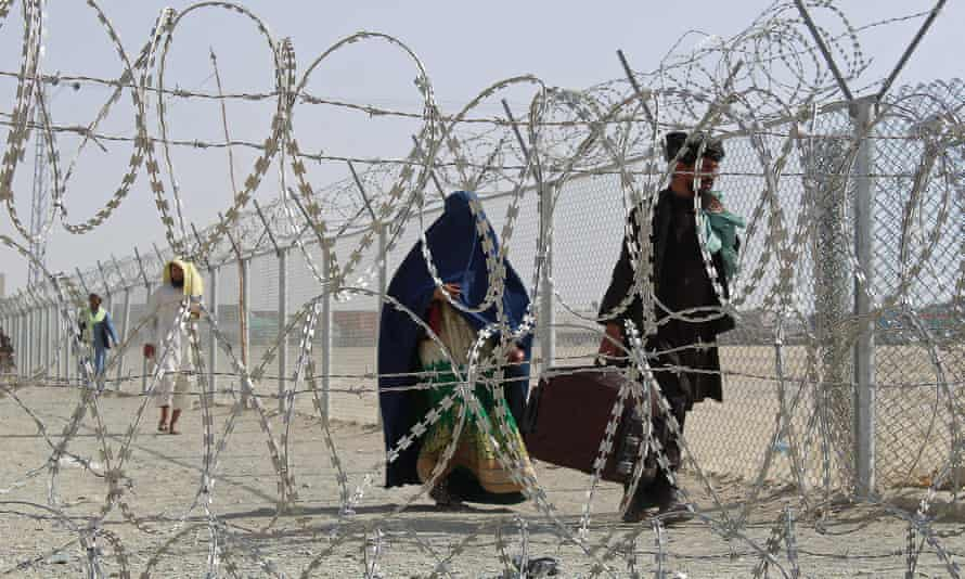 Afghans walk along a fenced corridor after crossing into Pakistan near Chaman on Saturday.