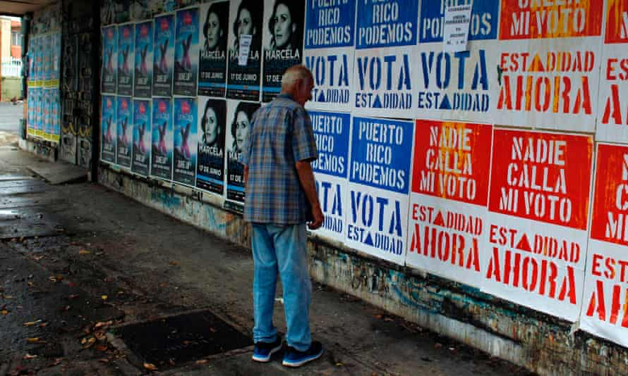 A man reads campaign posters in San Juan before the vote on Puerto Rican statehood.
