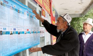 A man reads information about the candidates for parliament at a polling station in Belovodsk town.