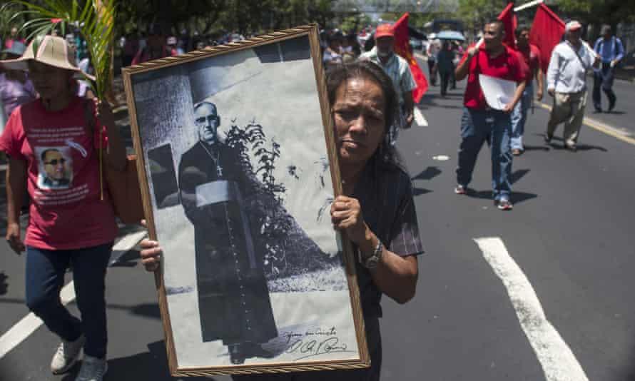 A woman with a portrait of Óscar Romero in San Salvador