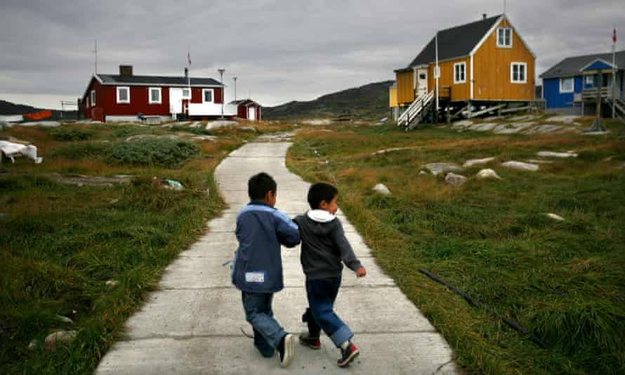 Two boys walking away from us in a Greenland village