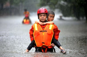 Changsha city, China: A man rescues a young boy from flooded areas caused by heavy rain