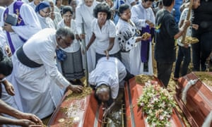 Relatives of the dead offer their prayers during funerals in Negombo.