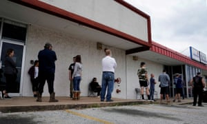 People who lost their jobs wait in line to file for unemployment in Fayetteville, Arkansas on 6 April 2020.
