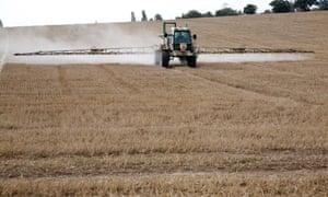 a tractor sprays a field
