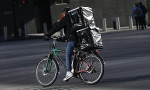 A man making deliveries rides an electronic bike in New York