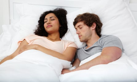 A sleeping couple in bed.