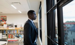 Black man in suit looking out a window