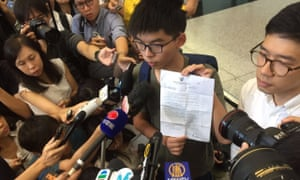 Joshua Wong talking to the press after arriving back in Hong Kong.