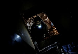 Sakae Kato holds a flashlight in his mouth as he climbs up a ladder on to the second floor of an abandoned house he converted into a cat shelter