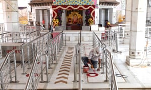 A man paints circles on the floor of a temple in New Delhi for devotees to maintain social distancing as the government plans to open places of worship as part of the easing of the nationwide Covid-19 lockdown.
