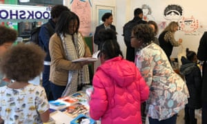 Customers in #ReadTheOnePerCent popup bookshop in Brixton Market that only sells books with non-white protagonists