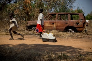 Two young girls walk past a burnt-out vehicle towards a water point in the town of Malakal