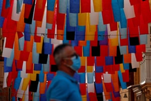 A man wearing a mask walks past a street installation made of coloured banners in Valletta, Malta on 11 November, 2020.