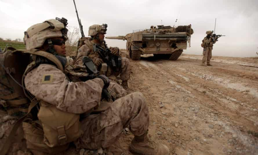 US marines with 1/3 marine Charlie Company patrol past a Danish army Leopard 2A5EK tank as they clear Improvised Explosive Device (IED)s from a main route in Trikh Nawar on the North Eastern outskirts of Marjah on February 21, 2010.