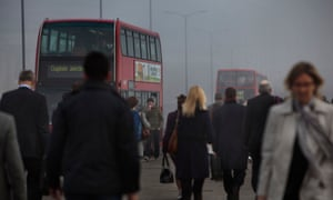 Commuters and traffic crossing London Bridge on a smoggy morning.