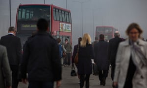 Commuters and busy traffic crossing London Bridge on a smoggy morning