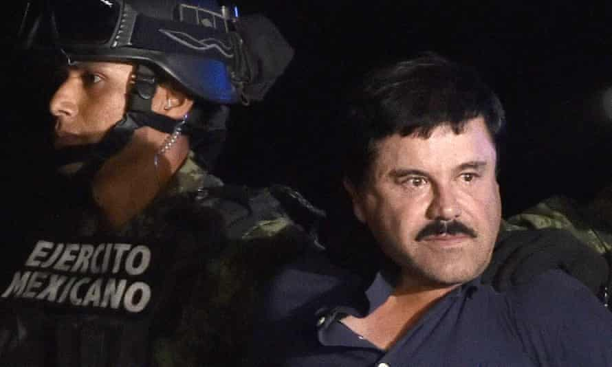 """Drug kingpin Joaquin """"El Chapo"""" Guzman is escorted into a helicopter at Mexico City's airport following his recapture during an intense military operation in Los Mochis, in Sinaloa State."""