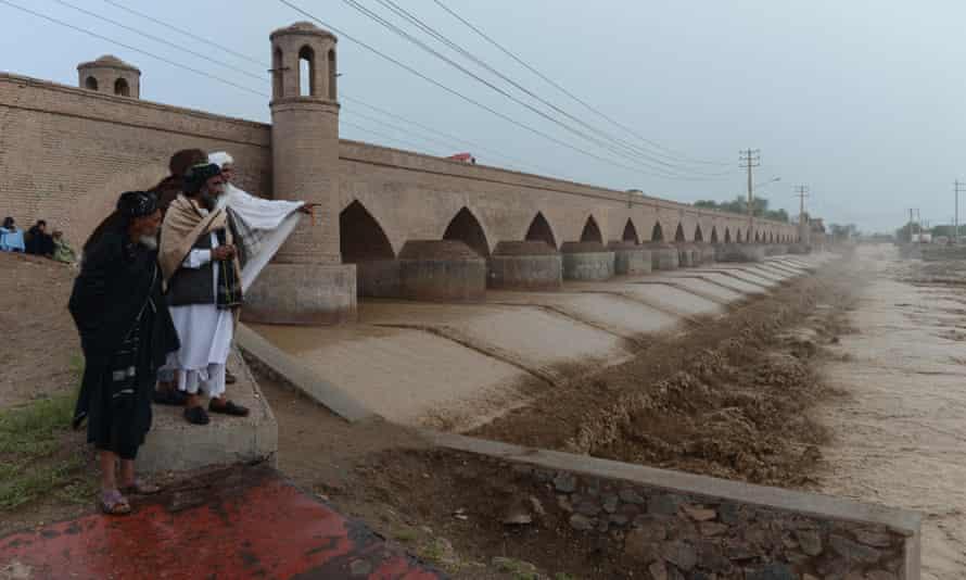 People look at flood waters in Guzara district,Herat province, Afghanistan