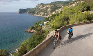 Mature man and mid adult woman riding bicycle in Ibiza, Spain