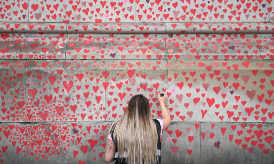 A woman adds a heart to the National Covid Memorial Wall in London.