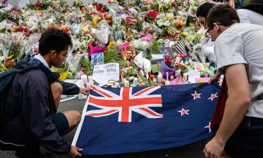 NZEALAND-ATTACK-MOSQUEStudents display the New Zealand national flag next to flowers during a vigil in Christchurch on March 18, 2019, three days after a shooting incident at two mosques in the city that claimed the lives of 50 Muslim worshippers. - New Zealand will tighten gun laws in the wake of its worst modern-day massacre, the government said on March 18, as it emerged that the white supremacist accused of carrying out the killings at two mosques will represent himself in court. (Photo by ANTHONY WALLACE / AFP)ANTHONY WALLACE/AFP/Getty Images