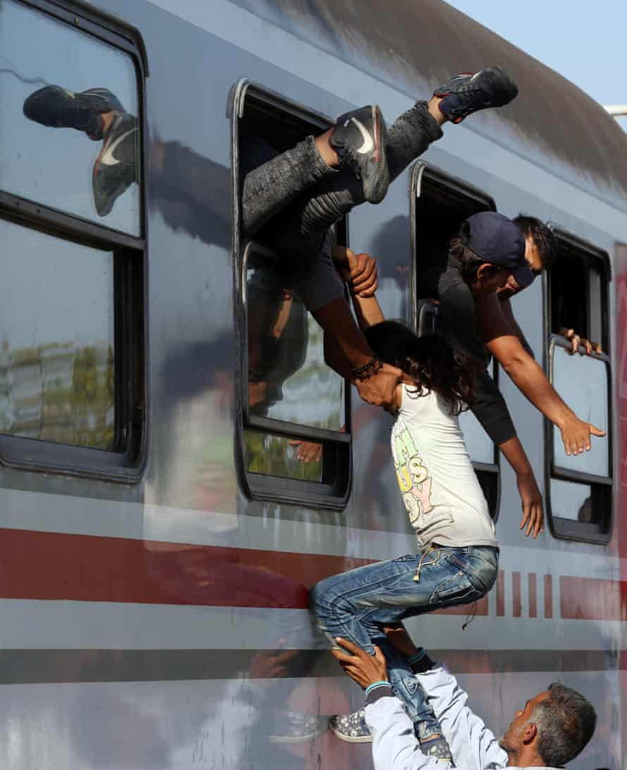 Refugees trying to get on to a train at the Croatia-Serbia border, September 2015.