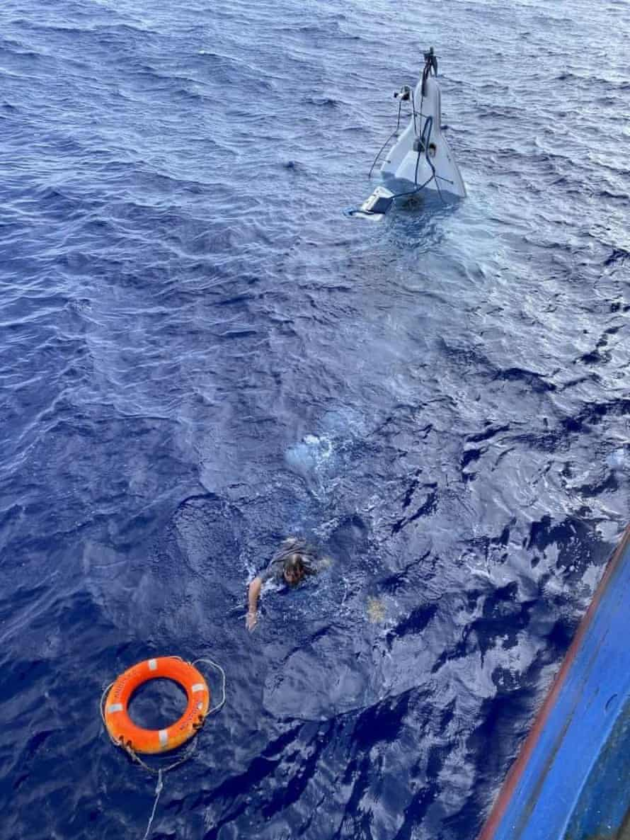 Stuart Bee swimming from his capsized boat to a buoy thrown by the crew of the Angeles cargo ship