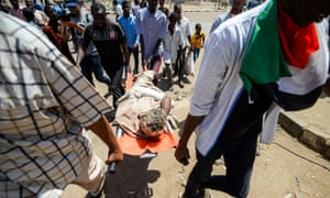 Sudanese protesters carry an injured man on a stretcher after the attack in Khartoum.