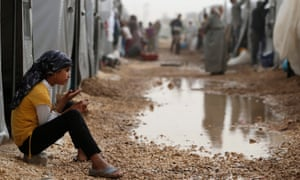 A file picture dated 11 October 2014 shows a Syrian refugee girl sitting in front of a tent in a refugee camp after she fled from Islamic State violence at Suruc district, Sanliurfa, Turkey.