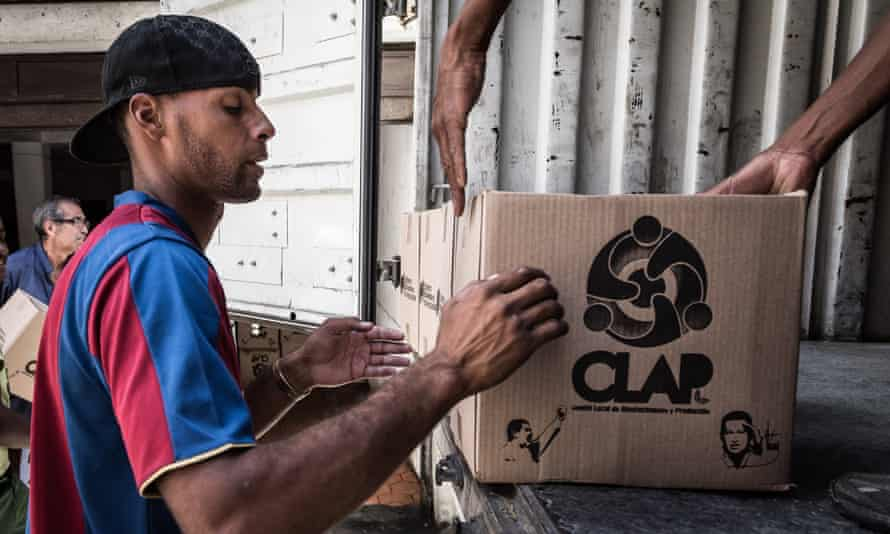"""Men unload Clap boxes containing basic food supplies in Petare. Clap boxes are one of the measures implemented by Nicolás Maduro's government to fight what they term as the """"economic war"""""""