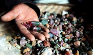 A Congolese mineral trader displays semi-precious tourmaline gem stones - used in laptops, mobile phones and jewellery, in eastern Congo July 24, 2010.