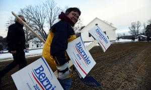 A supporter of US Democratic presidential candidate Bernie Sanders arrives with campaign posters outside the town hall as local residents vote for the first US presidential primary in Canterbury, New Hampshire.