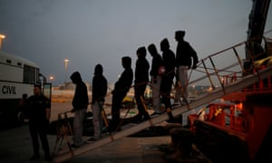 Migrants disembark from a rescue boat before being led into a police bus after arriving at the port of Algeciras, Spain, having been intercepted in the Strait of Gibraltar