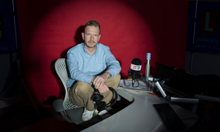 James O'Brien in his studio, squatting on his chair