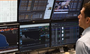 A trader looks at screens of financial data in the City of London