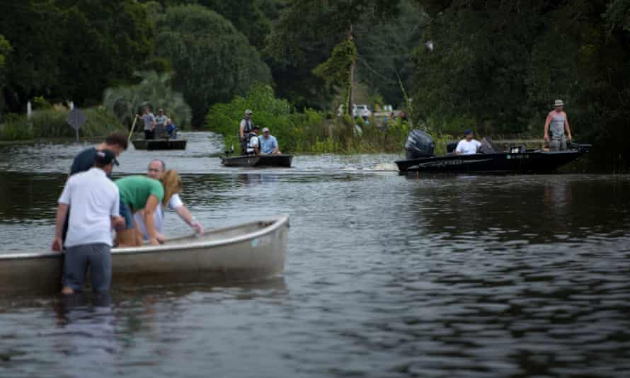 People use boats to access a neighborhood after flooding August 16, 2016