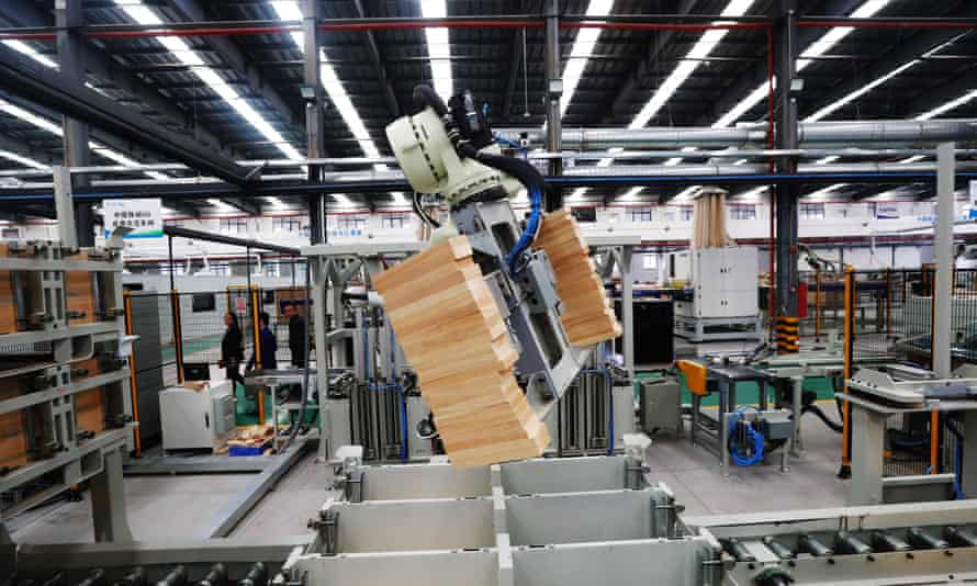 A robotic arm moves wood bricks at a factory in Ganzhou in China