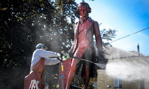 A worker cleans with a high pressure water jet red paint on the statue of Swiss banker, merchant and philanthropist David de Pury in Neuchatel.